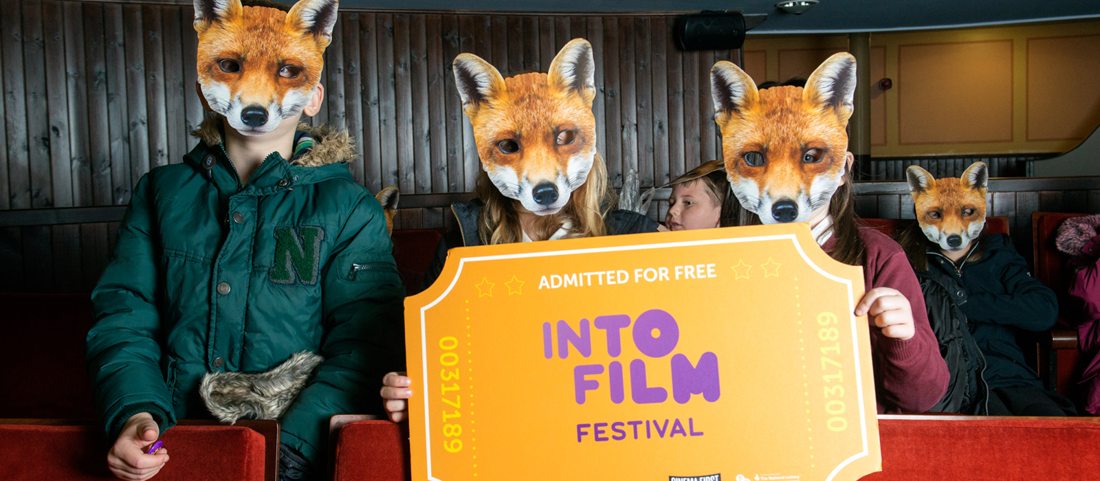 Young people with fox masks on holding up Into Film festival sign