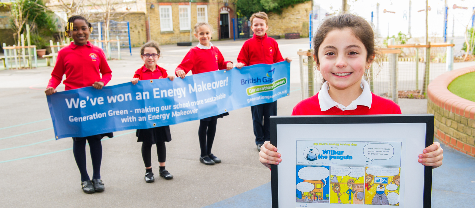 Young schoolchildren holding up British Gas banner and winning entry