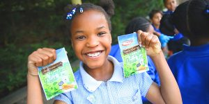 Schoolgirl holding Birds Eye pea seeds and smiling